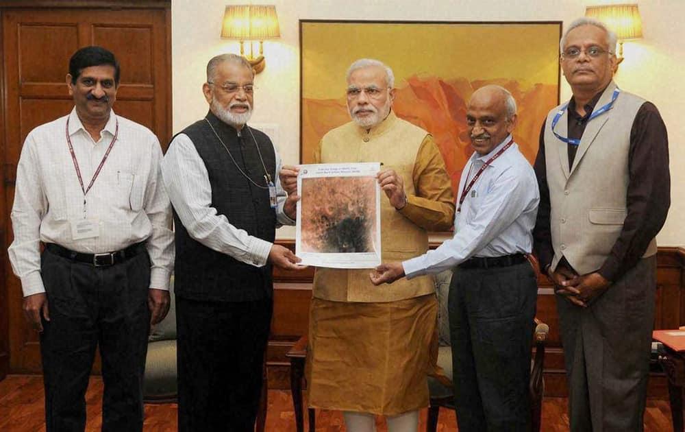 ISRO Chairman K Radhakrishnan presents an image of the surface of Mars taken by Mangalyaan to Prime Minister Narendra Modi.