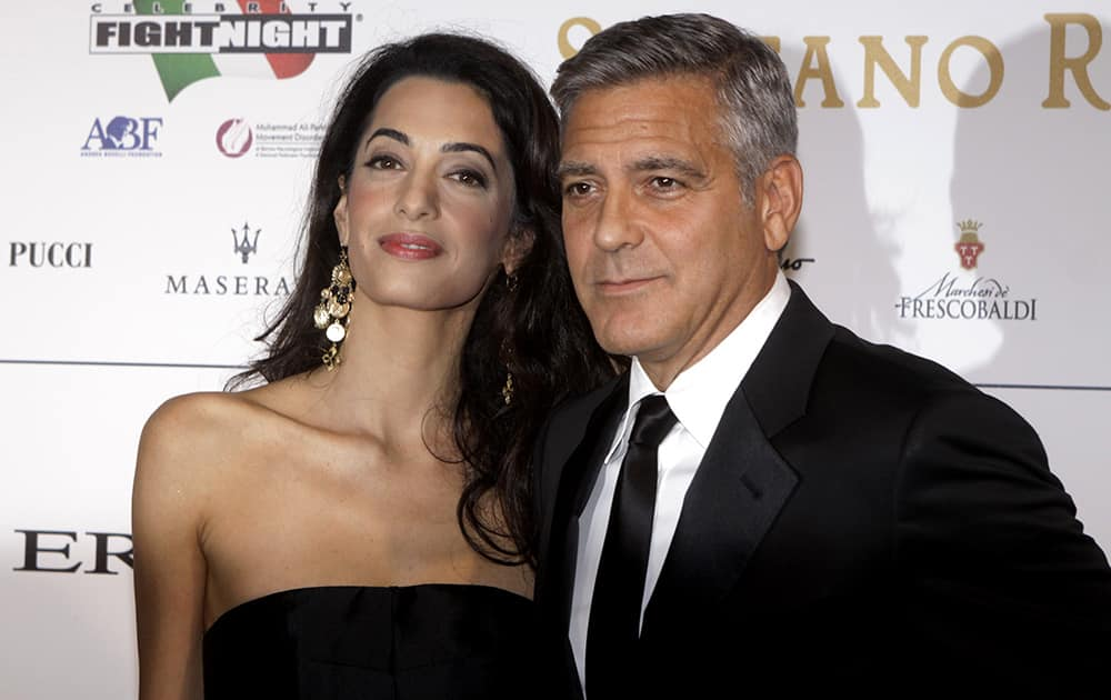 File Photo: George Clooney and his fiancee Amal Alamuddin pose for photographers as they arrive for the 'Celebrity Fight Night' foundation gala dinner, in Florence, Italy.