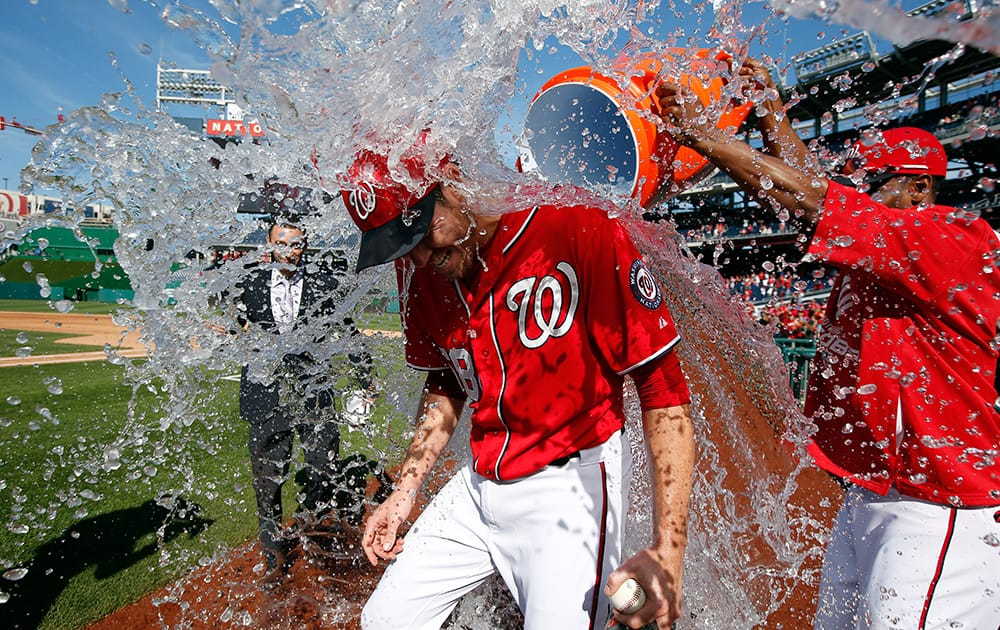 Washington Nationals starting pitcher Doug Fister, left, is doused with water by Michael Taylor after the first baseball game of a doubleheader at Nationals Park