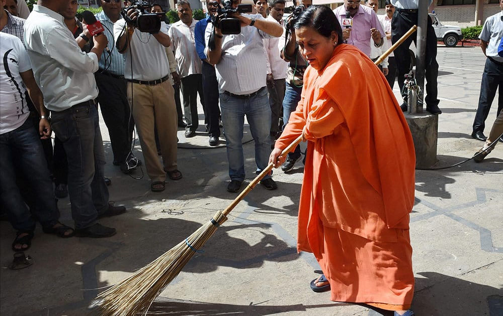 Union Water Resources Minister Uma Bharti sweeps as she takes part in Swachh Bharat Abhiyan' (Clean India Mission) at Shram Shakti Bhavan, in New Delhi.