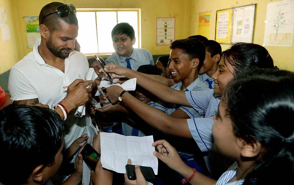 Cricketer Shikhar Dhawan signing autographs for students during his visit to a school in Kolkata.