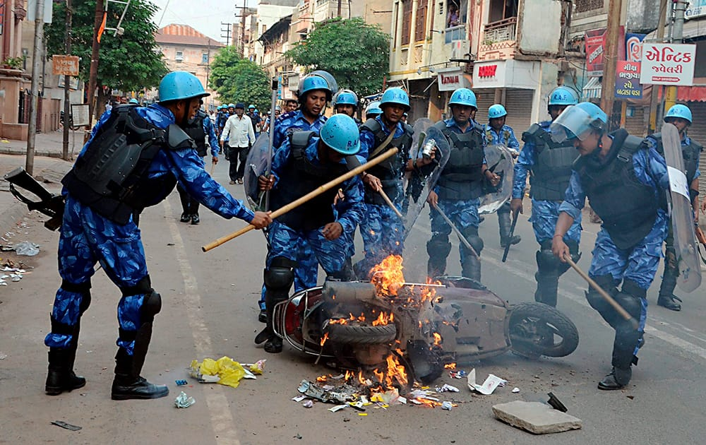 RAF personnel try to douse fire on a scooter following fresh communal violence in Vadodara.