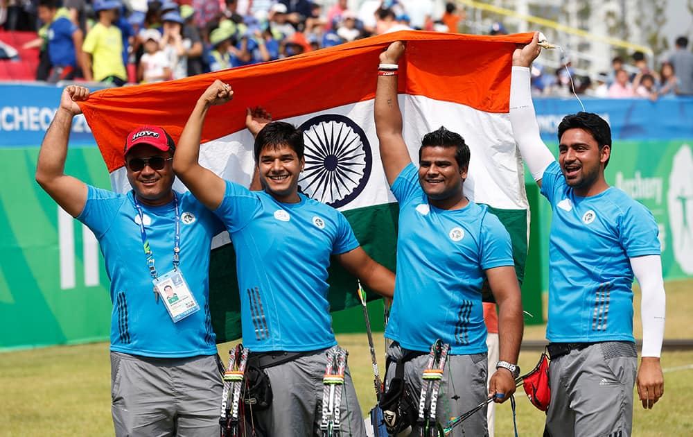 India's team members Sandeep Kumar, Raijat Chauhan, Abhishek Verma celebrate with their coach after winning the compound men's team gold medal archery match at the 17th Asian Games in Incheon.