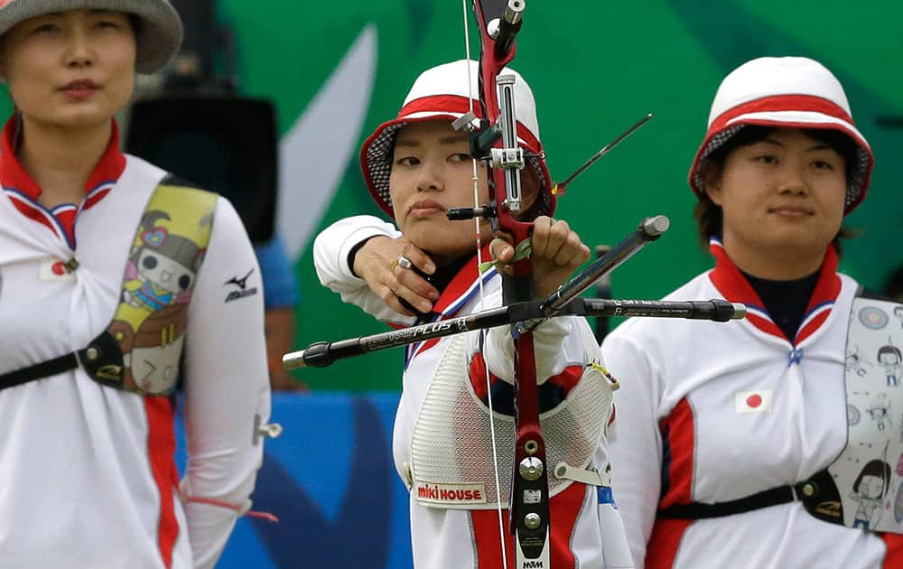 Kaori Kawanaka of Japan competes as her team mates Ren Hayakawa and Yuki Hayashi look on during their Recurve Women's Team archery bronze medal match against India at the 17th Asian Games at Gyeyang Gymnasium in Incheon, South Korea.