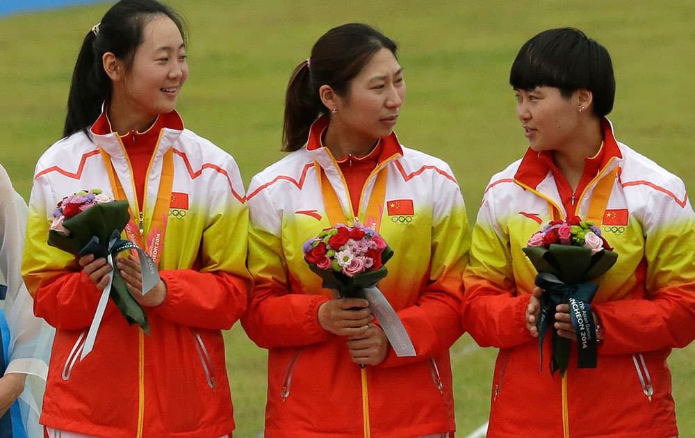 Fom left to right, China's Zhu Jueman, Xu Jing and Cheng Ming stand on the podium during the medal ceremony after winning the silver medal at the Recurve Women's Team archery competition at the 17th Asian Games in Incheon, South Korea.