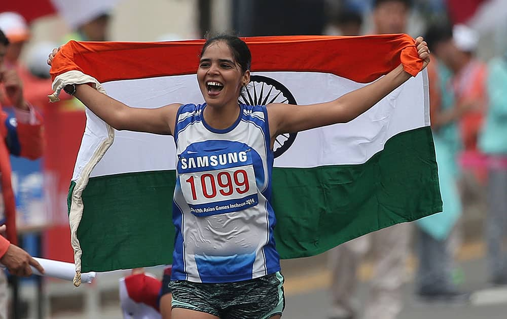 India's Kaur Khushbir holds her national flag after taking second place in the women's 20km race walk at the 17th Asian Games in Incheon, South Korea.