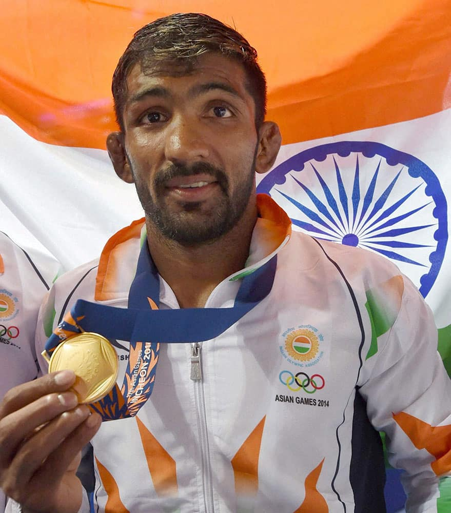 India`s Yogeshwar Dutt poses with gold medal after winning the mens 65 kg freestyle wrestling match at Dowon Gymnasium Stadium at Asian Games.