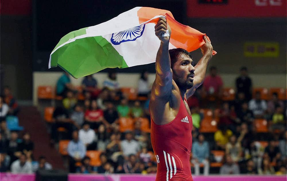 Indias Yogeshwar Dutt holds the tricolour after defeating Tajikistans Zalimkhan Yusupov, winning gold medal in the mens 65 kg freestyle wrestling match at Dowon Gymnasium Stadium at 17th Asian Games.