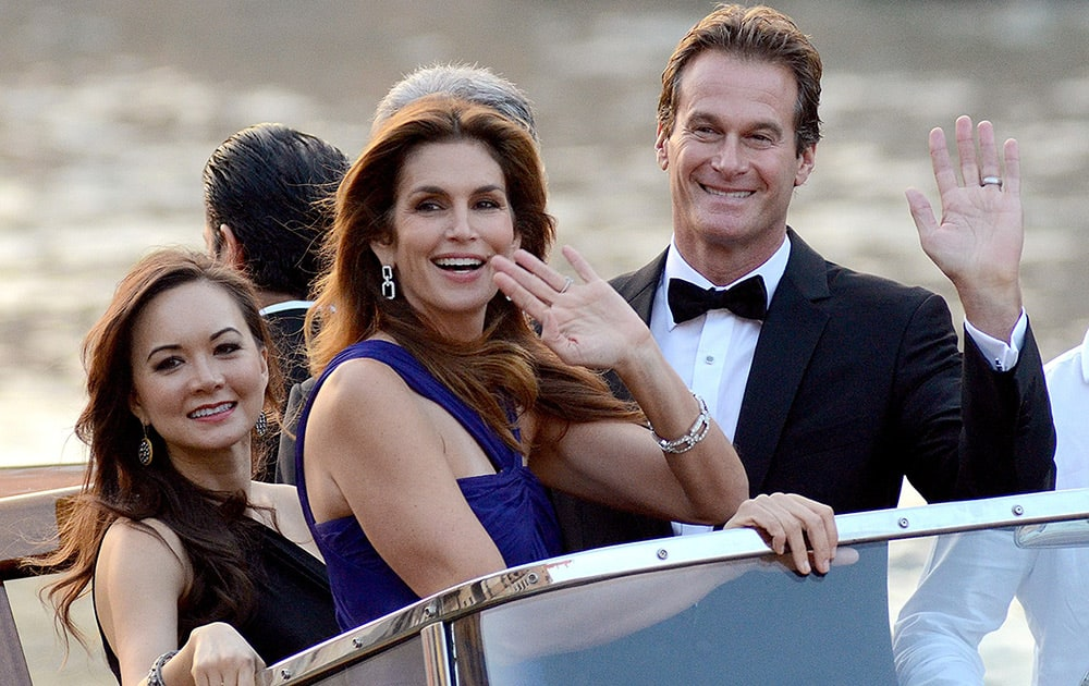 Cindy Crawford and Rande Gerber wave from a boat as they go to George Clooney's wedding with Amal Alamuddin, in Venice, Italy.