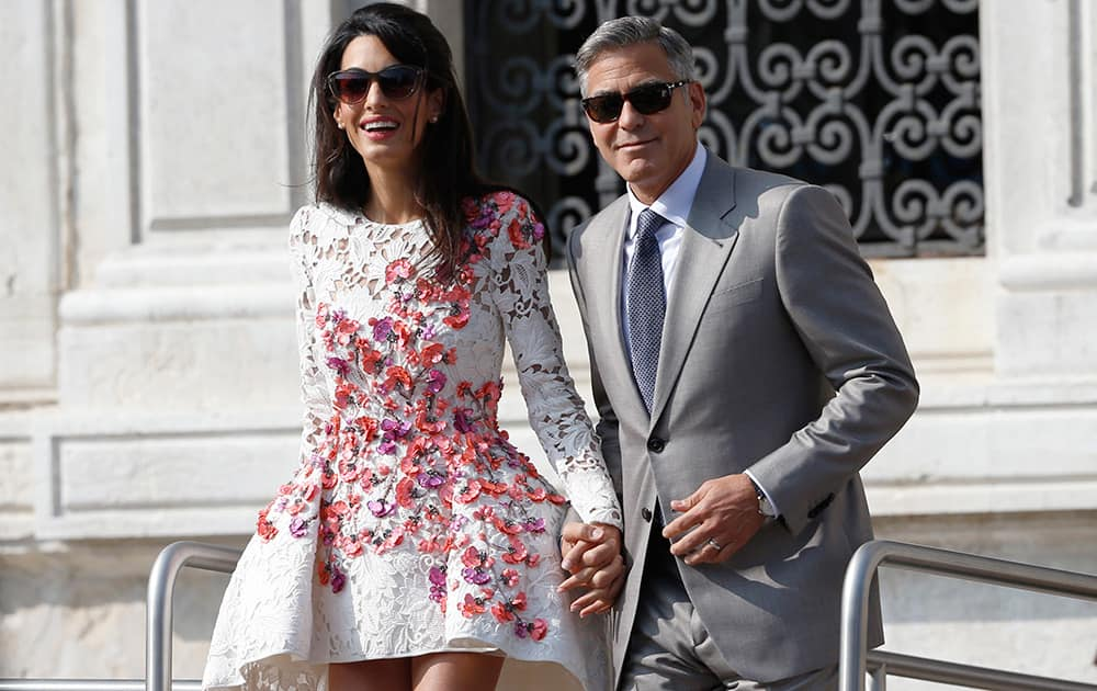 George Clooney is flanked by his wife Amal Alamuddin as they leave the Aman luxury Hotel in Venice, Italy.
