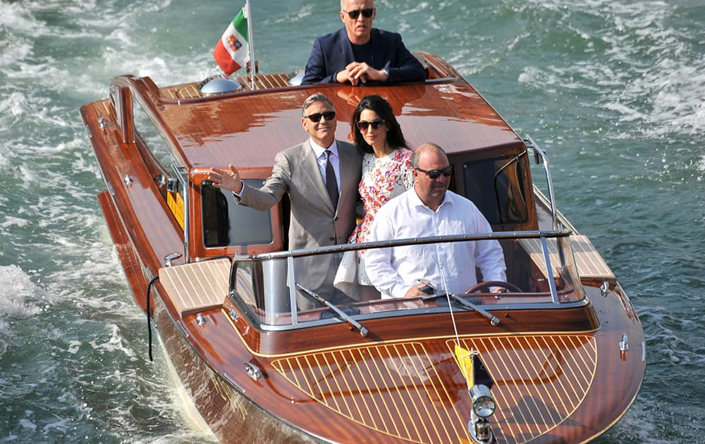 George Clooney waves as he cruises the Grand Canal on a boat with his wife Amal Alamuddin, after leaving the Aman luxury Hotel in Venice, Italy.