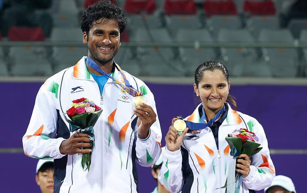 Gold medal winners Sania Mirza and Saketh Sai Myneni celebrate after winning the mixed doubles tennis match at the 17th Asian Games in Incheon, South Korea.