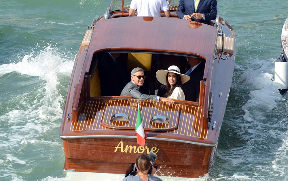 George Clooney, flanked by his wife Amal Alamuddin, sit on a water-taxi after leaving the city hall in Venice, Italy.