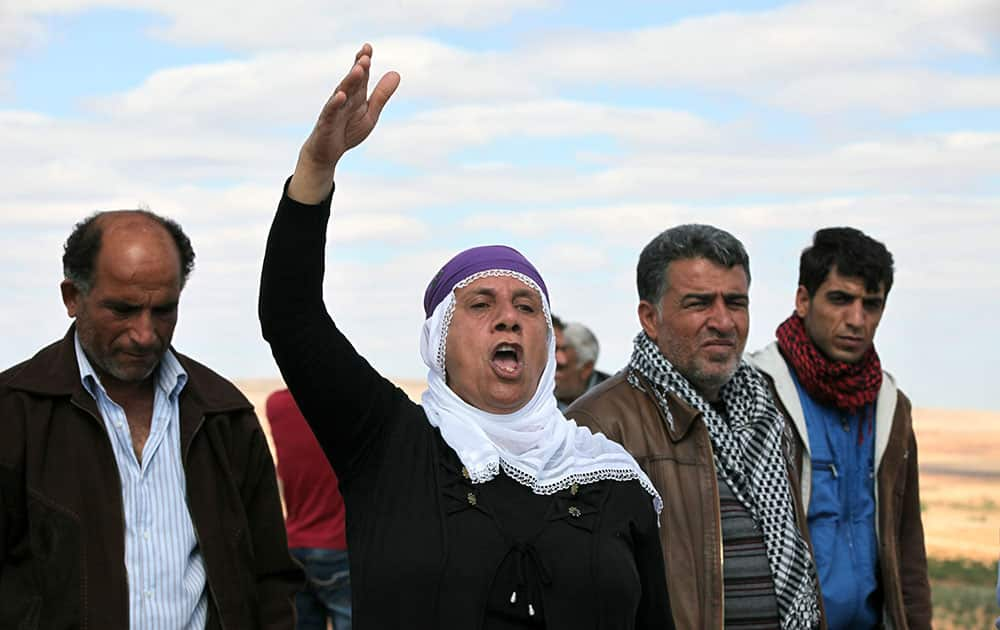 A woman shouts slogans as Turkish Kurds watch the fighting between Islamic militants and Kurdish forces to the west of Kobani, Syria, at the Turkey-Syria border near Suruc, Turkey.