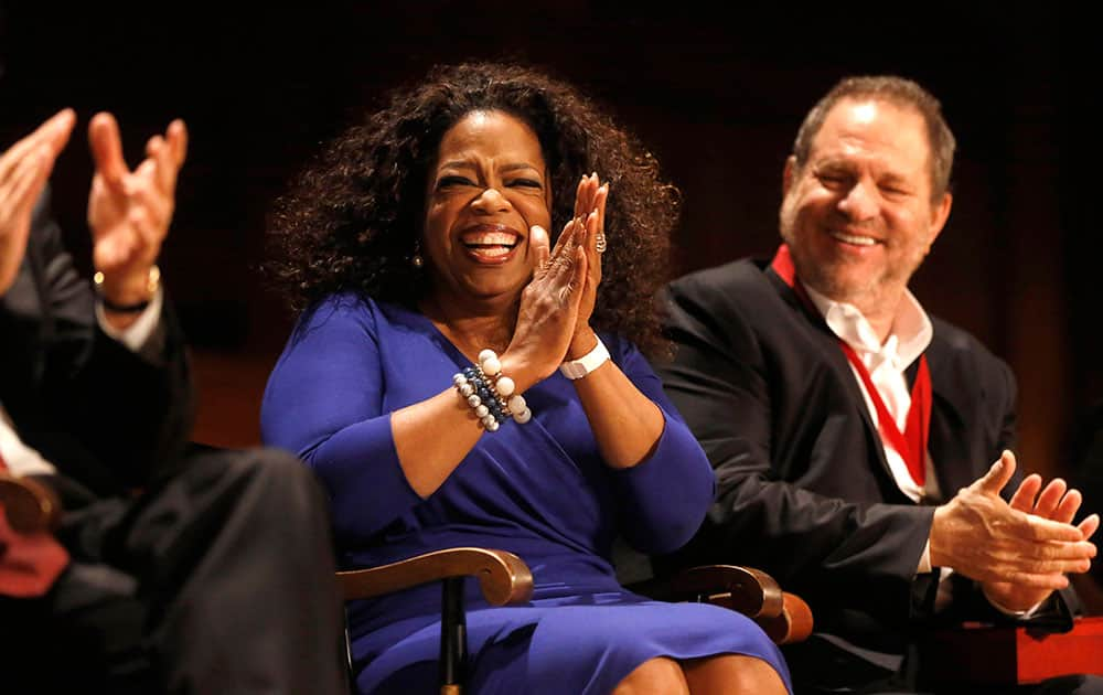 Actor, talk show host and philanthropist Oprah Winfrey, center, applauds along with film producer Harvey Weinstein, right, as Winfrey is introduced moments before accepting the W.E.B. Du Bois medal during ceremonies, on the campus of Harvard University, in Cambridge, Mass.