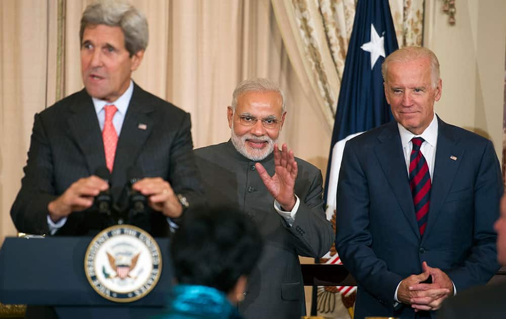 Indian Prime Minister Narendra Modi, flanked by Secretary of State John Kerry and Vice President Joe Biden, waves to a person in the audience during a luncheon at the State Department in Washington