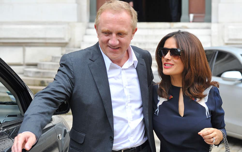 Mexican actress Salma Hayek and her husband Francois-Henri Pinault, CEO of luxury group Kering, leave after Stella McCartney's Spring/Summer 2015 ready-to-wear fashion collection presented in Paris