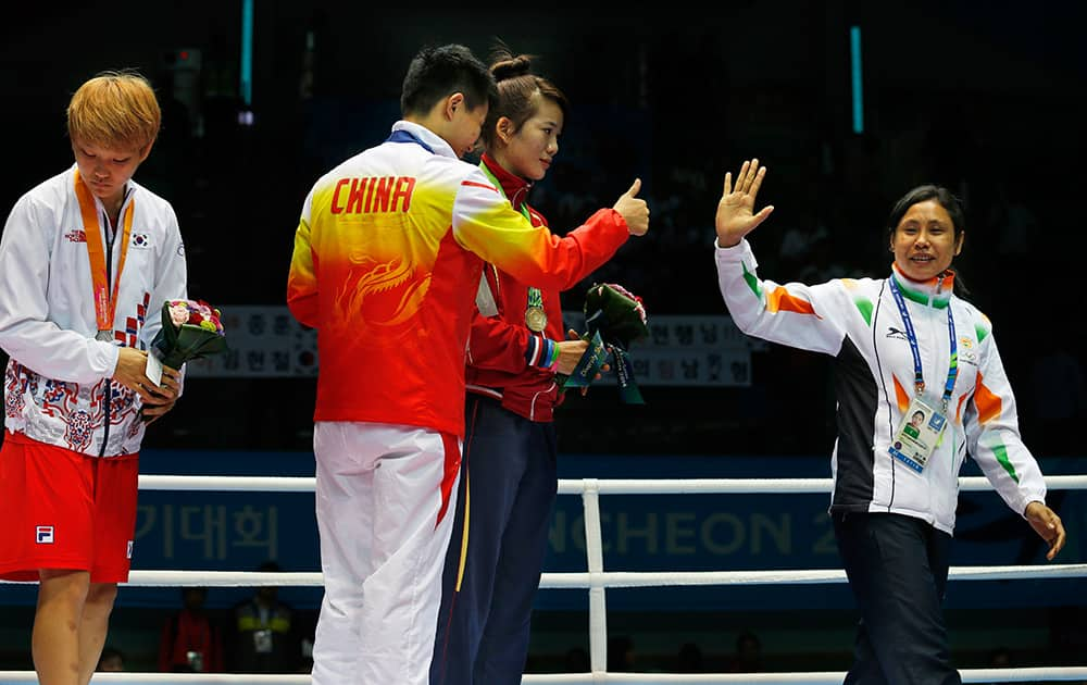 India's L. Sarita Devi, right, waves and leaves the podium, as gold medallist China's Yin Junhua gestures to her watched by bronze medalist Vietnam's Thi Duyen Luu, and silver medallist South Korea's Park Ji-na stands by the side, after Devi refused her bronze medal during the medal ceremony for the women's light 60-kilogram division boxing at the 17th Asian Games in Incheon, South Korea.