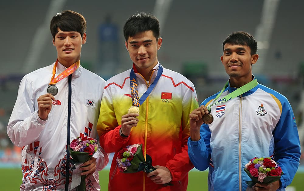Gold winner China's Xie Wenjun, center, silver winner South Korea's Kim Byoung, left and bronze winner Thailand's Jamras Rittidet pose during the medal ceremony of men's 110m hurdles event at the 17th Asian Games in Incheon, South Korea.