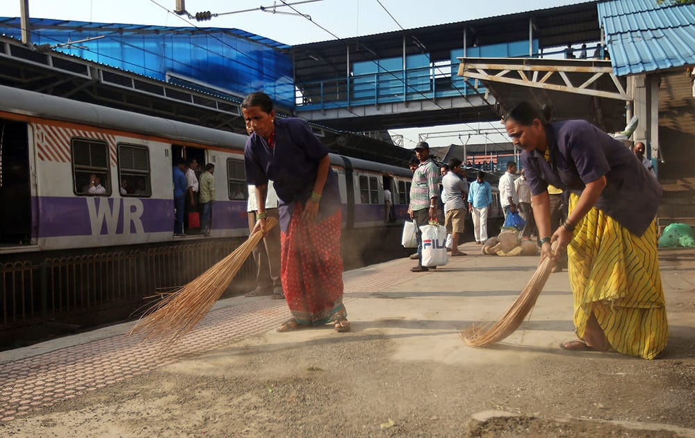 Workers clean a train station in Mumbai.