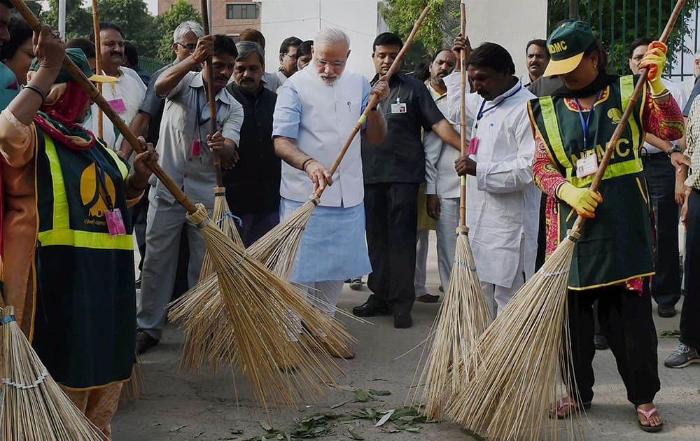 Prime Minister Narendra Modi wields a broom with NDMC workers to launch Swachh Bharat Abhiyan in Valmiki Basti in New Delhi.