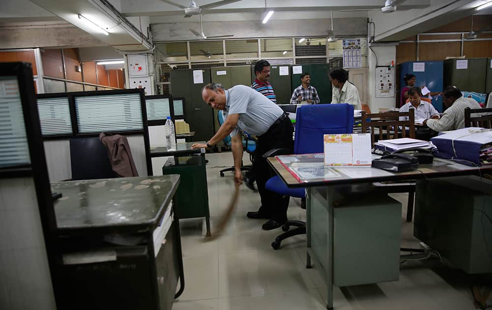 An Indian railways official cleans his office in Mumbai.