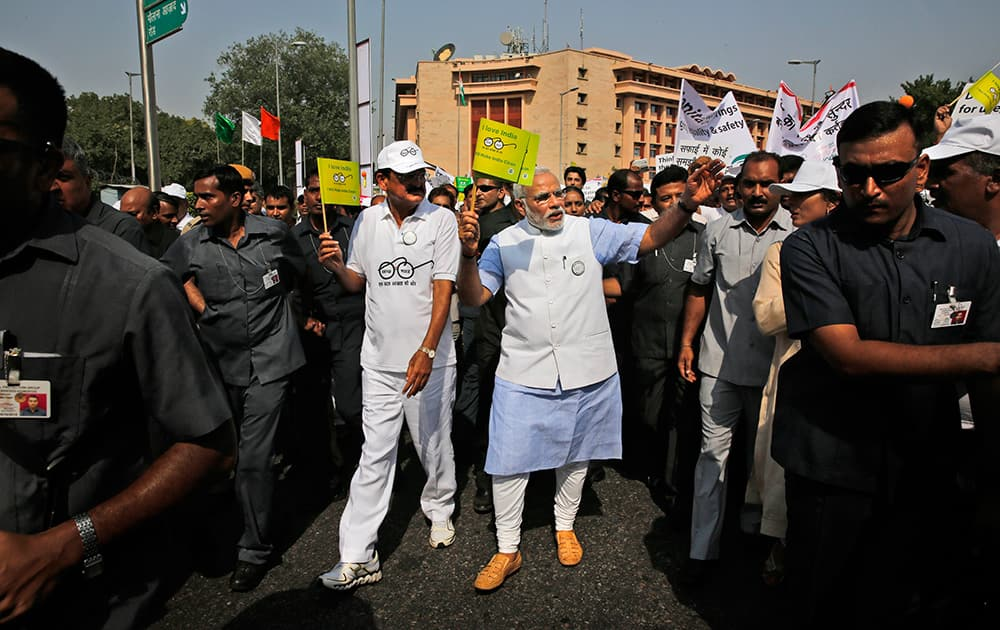 Prime Minister Narendra Modi, centre, waves a flag as he joins others in a walkathon as part of launching a nationwide cleanup campaign in New Delhi.