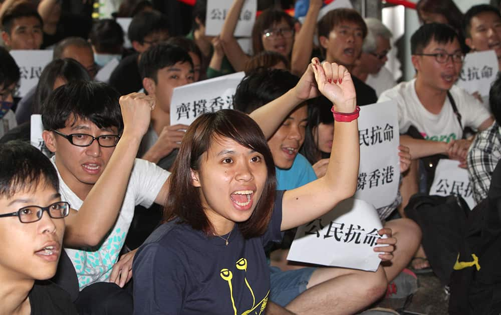 Hong Kong and Taiwanese student demonstrators shout slogans in support of pro-democracy protests taking place in Hong Kong at the Hong Kong Economic, Trade and Cultural Office in Taipei, Taiwan.