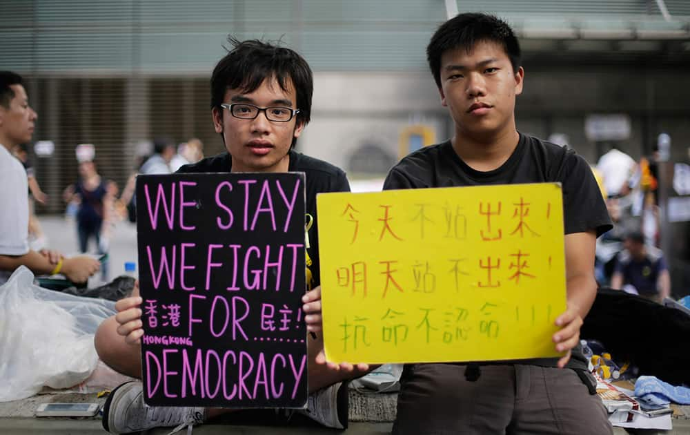 Student protesters sit with signs on their fight for democracy in Hong Kong.