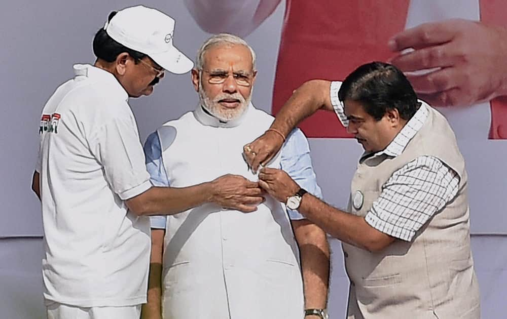 Union ministers Nitin Gadkari and M Venkaiah pinning a badge on Prime Minister Narendra Modis jacket during the launch of nationwide cleanliness campaign, the Swachh Bharat Mission at Rajpath in New Delhi.