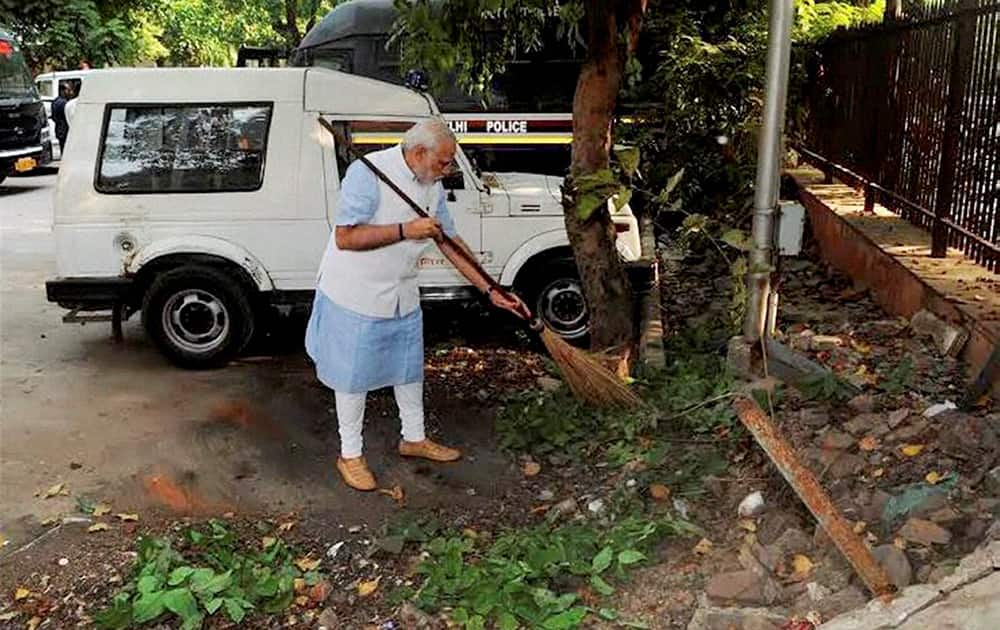 Prime Minister Narendra Modi wields the broom during a surprise visit to the Mandir Marg Police Station after launch of Swachh Bharat Abhiyan in New Delhi.