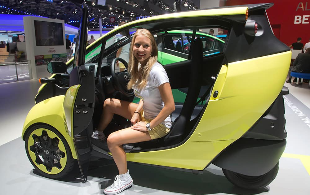 A hostess get out of a Toyota i - Road electric car during the press day at the Motor Show in Paris, France.