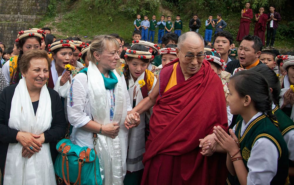 Tibetan spiritual leader the Dalai Lama, in red robe, talks to a school student watched by his fellow Nobel Laureates Shirin Ebadi, left and Jody Williams second left, as he arrives with them at the Tibetan Village School in Dharmsala.