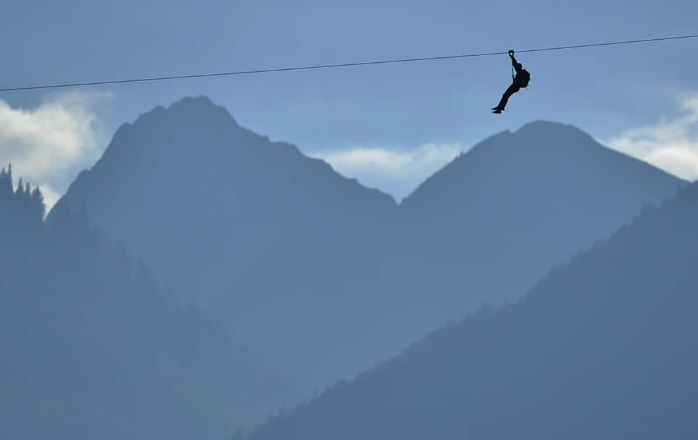 An unidentified man slips down the zip line back dropped by the mountains before the opening of the fair 'Foire du Valais' above the town of Martigny, Switzerland.