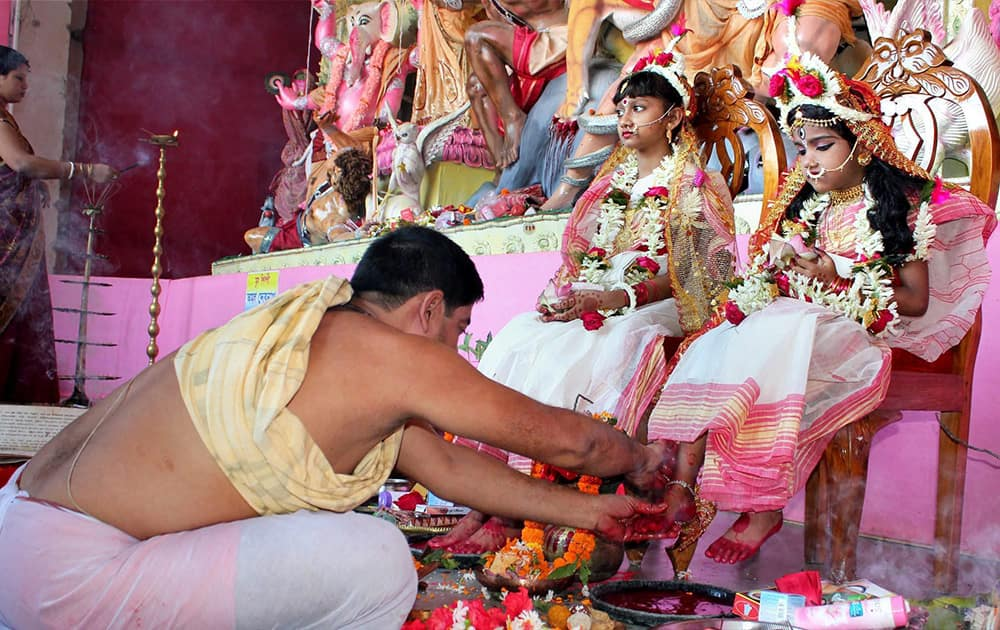 A priest performs rituals to young girls dressed as the Hindu goddess Durga during the Maha Ashtami celebrations at Balurghat in Dinajpur.