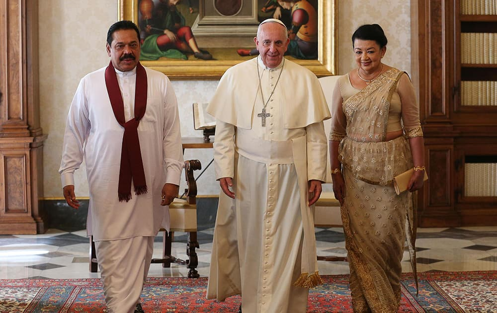 Pope Francis poses for photographers with Sri Lankan president Mahinda Rajapaksa, left, and his wife Shiranthi on the occasion of their private audience, at the Vatican.