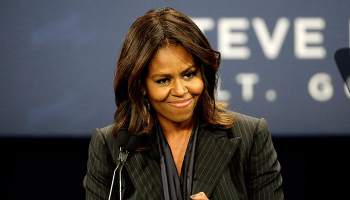 First lady Michelle Obama applauds as she mentions today is her wedding anniversary while campaigning for Massachusetts Democratic gubernatorial candidate Martha Coakley, during a Coakley for Governor campaign event at the Strand Theatre in Boston.