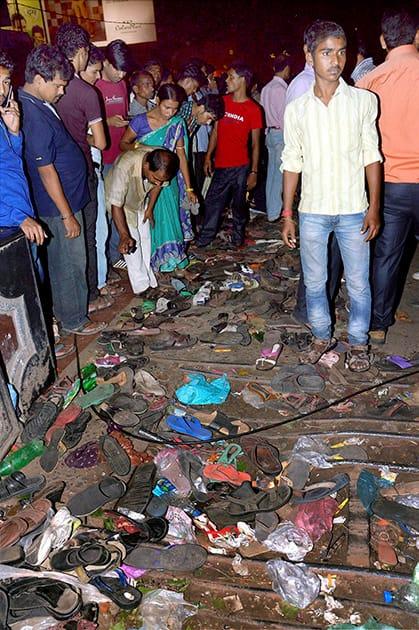 People stand near footwears of stampede victims during Dussehra function at Gandhi Maidan in Patna.