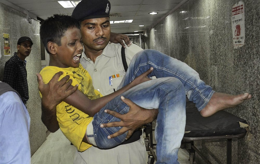 An Indian policeman carries a boy injured in a stampede in Patna.