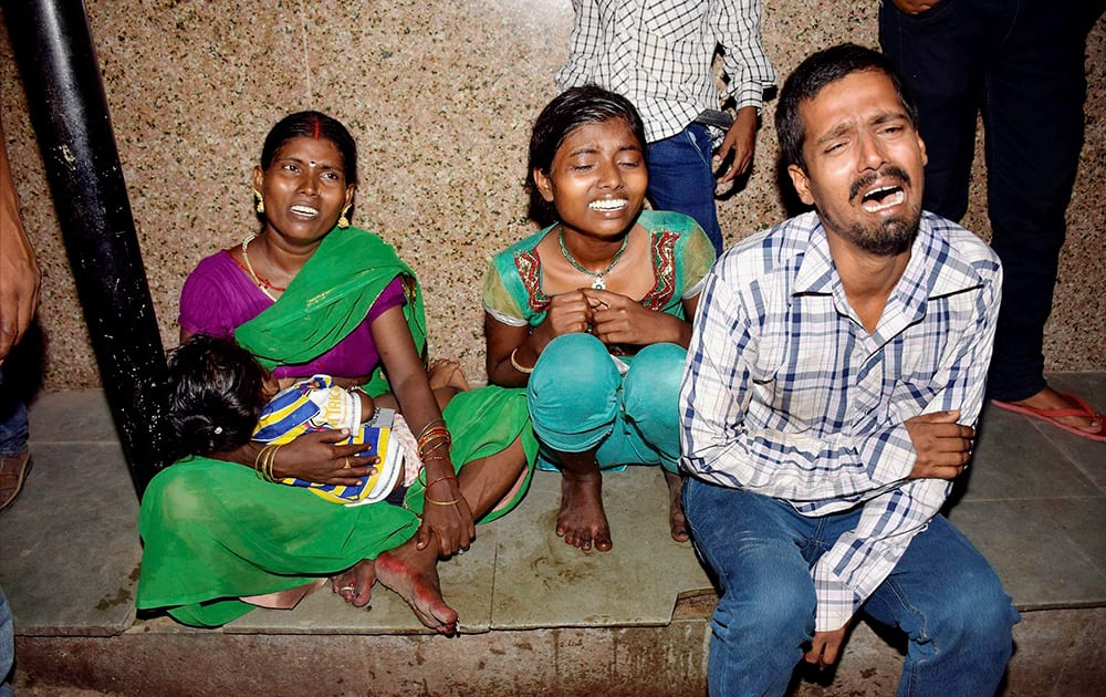 Family members of injured victims weep outside a hospital after a stampede occured during Dussehra function at Gandhi Maidan in Patna.