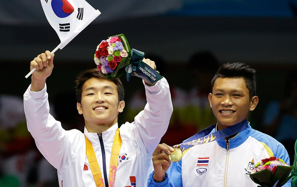 Thailand's Wuttichai Masuk holds his gold medal after defeating South Korea's Lim, left, Hyunchul in the men's light welter boxing final at the 17th Asian Games in Incheon, South Korea.