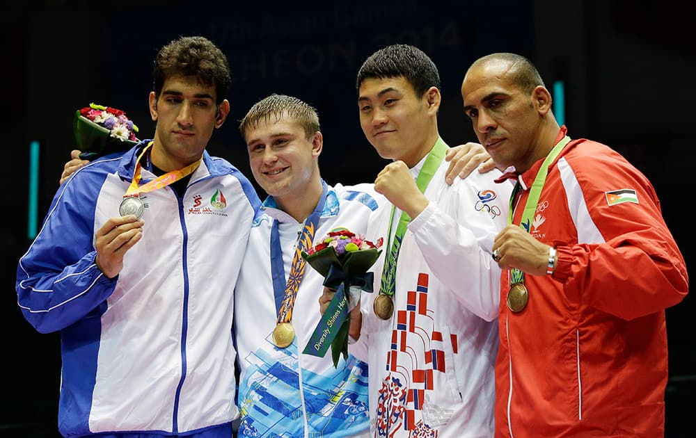 Gold medalist Kazakhstan's Anton Pinchuk, second left, stands with silver medalist Iran's Ali Mazaheri, left, and bronze medal winners South Korea's Park Namhyeong and Jordan's Ihab Almatbouli, right, following the medal ceremony for the men's heavy weight boxing final at the 17th Asian Games in Incheon, South Korea.