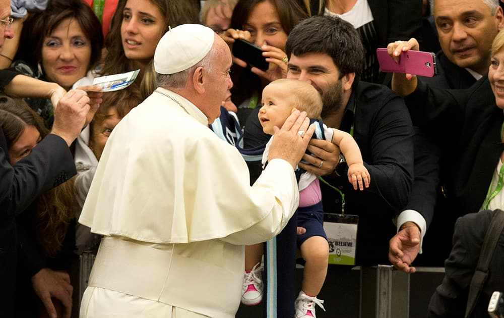 Pope Francis caresses a child as he arrives in the Paul VI hall on the occasion of the pontiff's meeting with paralympic athletes, part of the 'Believe to Be Alive' paralympic gala which will be held in Rome, at the Vatican City.
