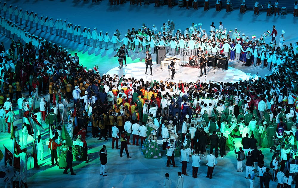 Athletes listen to a band perform during the closing ceremony of the 17th Asian Games in Incheon.