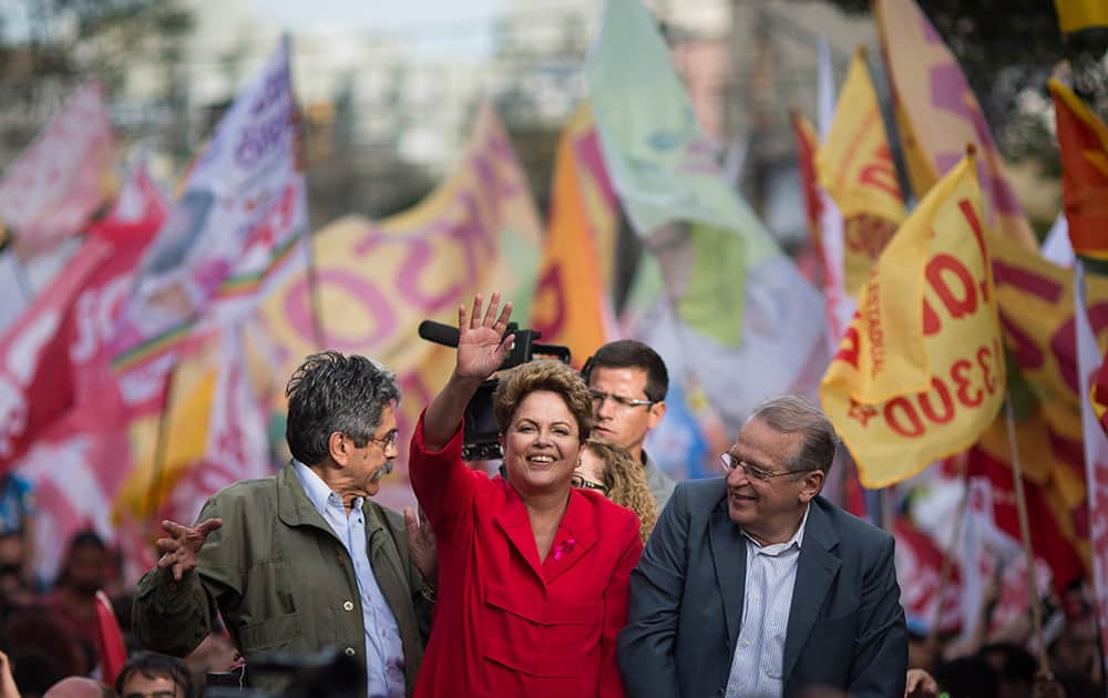 Brazil's President Dilma Rousseff, presidential candidate for re-election of the Workers Party, PT, greets supporters next to Olivio Dutra, PT candidate to the Senate, left, and Tarso Genro, candidate for Governor of Rio Grande do Sul, during a campaign rally in Porto Alegre, Brazil.