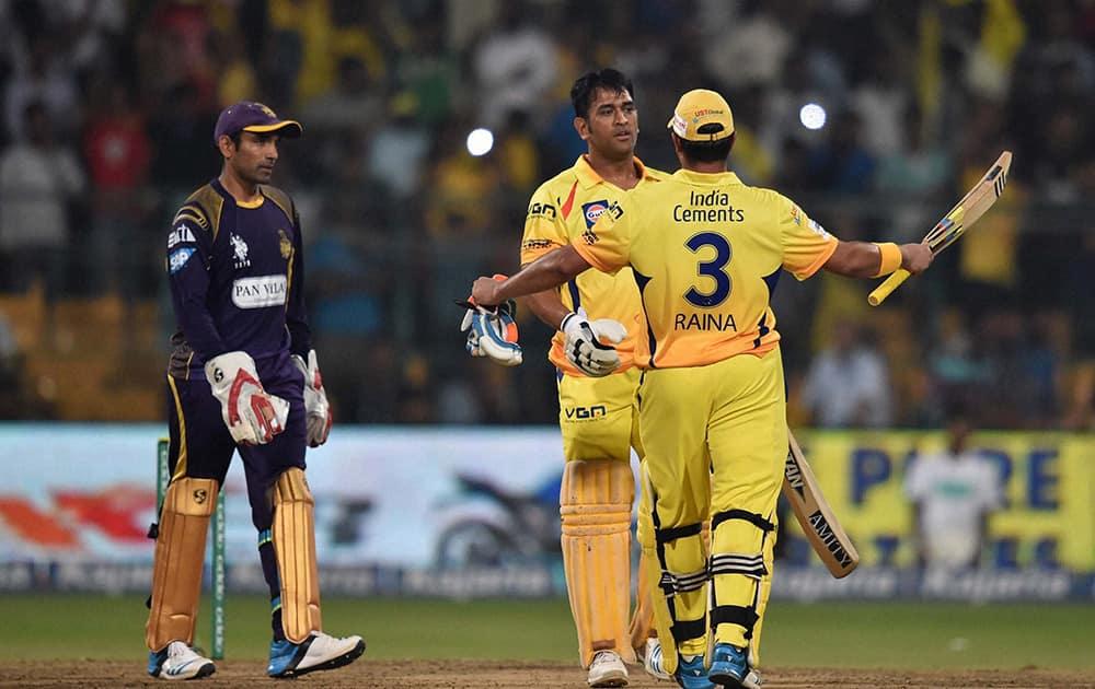 Chennai Super Kings batsman M S Dhoni and Suresh Raina celebrates the win during the CLT20 final match against Kolkata Knight Riders at Chinnaswamy Stadium in Bengaluru.