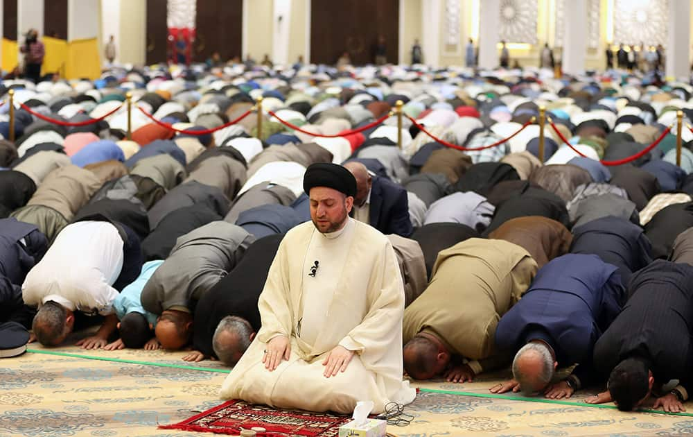 Ammar al-Hakim, leader of Iraq's largest Shiite party, the Supreme Islamic Iraqi Council, prays during Eid al-Adha or Feast of Sacrifice prayer, inside the party headquarters, in Baghdad, Iraq.