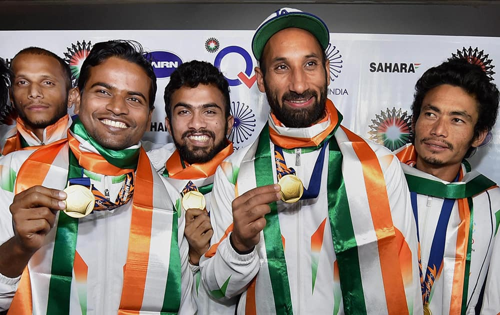 Players of the Asian Games gold medal winner Indian Hockey team with captain Sardar Singh pose with their medals upon arrival at IGI airport New Delhi.