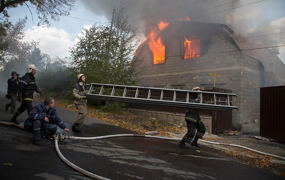 Firefighters try to extinguish a burning private house after shelling in the town of Donetsk, eastern Ukraine.