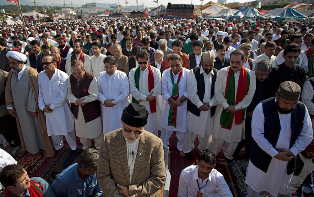 Pakistani Muslim cleric Tahir-ul-Qadri, front, leads the Eid al-Adha, or 'Feast of Sacrifice,' prayers, attended by Imran Khan, behind Qadri with sunglasses, outside a parliament building in Islamabad, Pakistan.